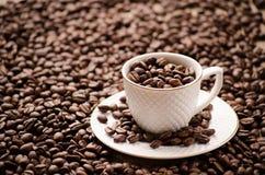 Tasse blanche avec une soucoupe sur des grains de café sur une table Photographie stock libre de droits