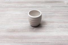 Tasse blanche dans l'intéret sur la table en bois brune grise Image stock