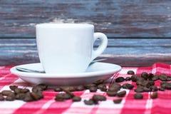 Tasse blanche de boisson chaude avec du café sur une nappe à carreaux blanche rouge près d'un mur en bois Pause-café française de image libre de droits