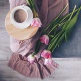 Tasse blanche de cacao, tulipes roses sur un sofa gris, vue supérieure image libre de droits