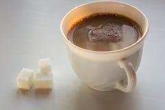 Tasse blanche de café noir avec du lait Trois morceaux de sucre raffiné images libres de droits