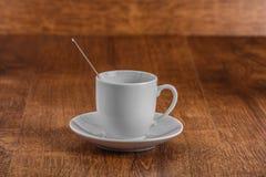 Tasse blanche de coffe avec la cuillère sur la soucoupe blanche sur le fond en bois de brun foncé Photographie stock