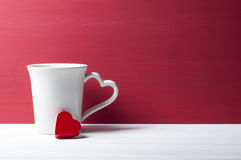 Tasse blanche de penchement de coeur rouge Concept de valentines Images libres de droits