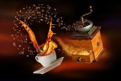 Tasse blanche de Porcelaine avec éclabousser le café et la broyeur sur le fond d'obscurité d'abrégé sur tache floue images stock