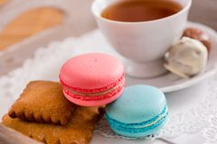 Tasse blanche de thé chaud, de macaronis et de biscuits sablés frais avec des bonbons à chocolat Goût de menthe et de fraise Sur  Image stock