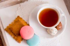Tasse blanche de thé chaud, de macaronis et de biscuits sablés frais avec des bonbons à chocolat Goût de menthe et de fraise Sur  Photo libre de droits