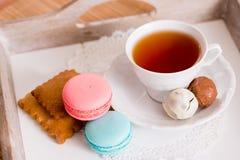 Tasse blanche de thé chaud, de macaronis et de biscuits sablés frais avec des bonbons à chocolat Goût de menthe et de fraise Sur  Photo stock