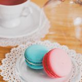Tasse blanche de thé chaud, de macaronis et de biscuits sablés frais Goût de menthe et de fraise Sur une serviette Félicitations  Images libres de droits