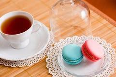 Tasse blanche de thé chaud, de macaronis et de biscuits sablés frais Goût de menthe et de fraise Sur une serviette Félicitations  Photo libre de droits