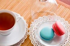 Tasse blanche de thé chaud, de macaronis et de biscuits sablés frais Goût de menthe et de fraise Sur une serviette Félicitations  Images stock