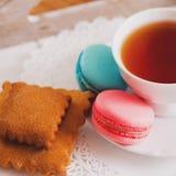 Tasse blanche de thé chaud, de macaronis et de biscuits sablés frais Goût de menthe et de fraise Sur une serviette Félicitations  Image libre de droits