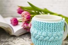 Tasse blanche de thé dans une caisse bleue tricotée avec un livre ouvert et avec les tulipes et les bonbons roses de fleurs, avec photos stock