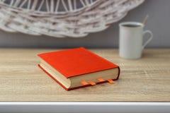 Tasse blanche de thé et un livre ouvert sur une table en bois Un pot rouge avec l'arbre vert à l'arrière-plan Photo stock