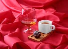 Tasse blanche du café et du cognac dans des verres, pralines sur le fond rouge Photo libre de droits