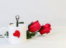 Tasse blanche et coeur rouge avec les roses rouges, d'isolement sur le backgr blanc Photo stock