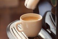 Tasse blanche se tenant sur la grille de la machine de café avec du café Photo stock