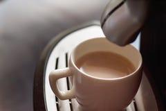 Tasse blanche se tenant sur la grille de la machine de café avec du café Photo libre de droits