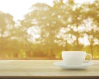Tasse blanche sur la table en bois au-dessus du fond de bokeh d'arbre Images stock