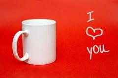 """Tasse blanche sur le fond rouge avec le  de you†d'amour de l'"""" I de signe Copiez l'espace pour l'inscription Verre blanc d'i Photographie stock libre de droits"""