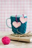 Tasse bleue dans le chandail rose avec des coeurs de feutre avec la boule du fil Photo libre de droits