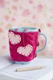 Tasse bleue dans le chandail rose avec des coeurs de feutre se tenant sur le carnet Photo stock