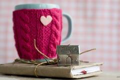 Tasse bleue dans un chandail rose se tenant sur un vieux carnet Image stock