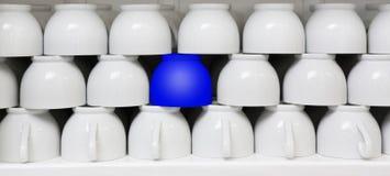 Tasse bleue parmi des tasses de café blanc Photo stock