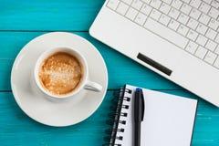 Tasse, bloc-notes et ordinateur portable de café sur le backgroun en bois de turquoise Images stock