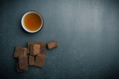 tasse brune de guimauve et de thé sur le fond foncé image stock