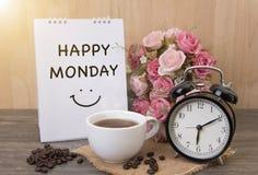 Tasse chaude de café et de réveil sur la table en bois avec la fleur rose Image stock