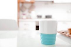 Tasse colorée de turquoise sur un comptoir de cuisine Photos stock