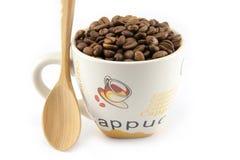 Tasse complètement de grains de café d'isolement Image libre de droits