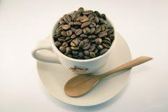 Tasse complètement de grains de café d'isolement Photographie stock libre de droits