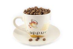 Tasse complètement de grains de café d'isolement Image stock