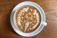 Tasse délicieuse de latte italien de café avec la décoration artistique de mousse étonnante de lait d'un dieu de hindi à la table photo libre de droits