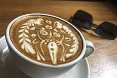 Tasse délicieuse de latte italien de café avec la décoration artistique de mousse étonnante de lait d'un dieu de hindi à la table images stock