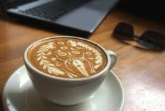 Tasse délicieuse de latte italien de café avec la décoration artistique de mousse étonnante de lait d'un dieu de hindi à la table image libre de droits