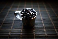 Tasse d'acier inoxydable de coffe avec des grains de café photo stock