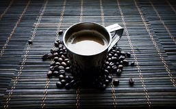 Tasse d'acier inoxydable de coffe avec des grains de café photographie stock