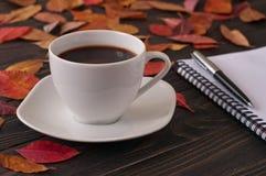 Tasse d'americano aromatique de café avec le bloc-notes et le stylo Images libres de droits