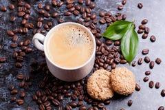 Tasse d'americano et biscuits sur le fond de grains de café Photographie stock