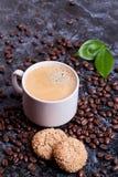 Tasse d'americano et biscuits sur le fond de grains de café Images libres de droits