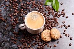 Tasse d'americano frais et biscuits sur le fond de grains de café Images stock