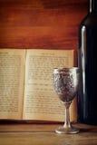 Tasse d'argent de shabbath de vintage de vin devant le livre de prière de torah Image libre de droits