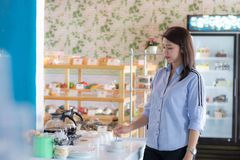 Tasse d'Attracive de caf? de versement femelle asiatique de bouilloire de fabricant de caf? au g?teau images stock