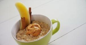 Tasse d'avoine avec le beurre d'arachide, bâtons 4k de banane et de cannelle banque de vidéos