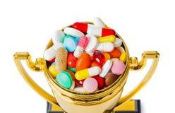 Tasse d'or de trophée avec des pilules photos libres de droits