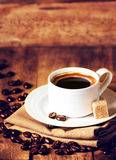 Tasse d'expresso avec la soucoupe blanche et les grains de café rôtis sur W Photo stock