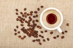 Tasse d'expresso et grains de café vides sur la toile Photo stock
