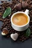 Tasse d'expresso sur des grains de café fond et bonbons au chocolat Image libre de droits